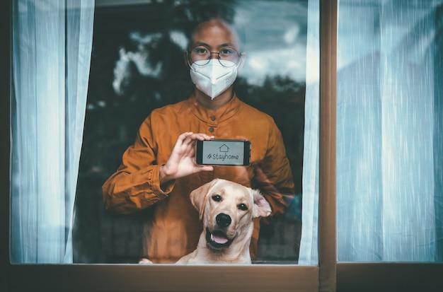 Asiatisches mädchen mit brille, das eine maske trägt, mit labrador-hund, der aus dem fenster schaut, ist gelangweilt, die krankheit allein zu hause festhalten und behandeln zu müssen. konzept heimquarantäne, prävention covid-19