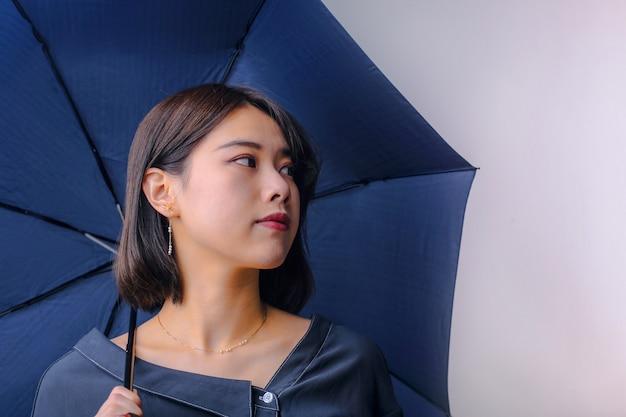 Asiatisches mädchen mit einem regenschirm