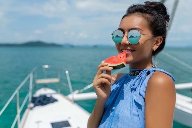 Asiatisches mädchen mit gläsern isst eine wassermelone auf einer yacht. luxusreisen. sommerferien.