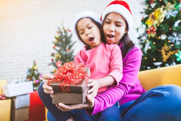 Asiatisches mädchen mit ihrer mutter, die schöne geschenkbox und überraschung mit geschenk in der weihnachtsfeier hält