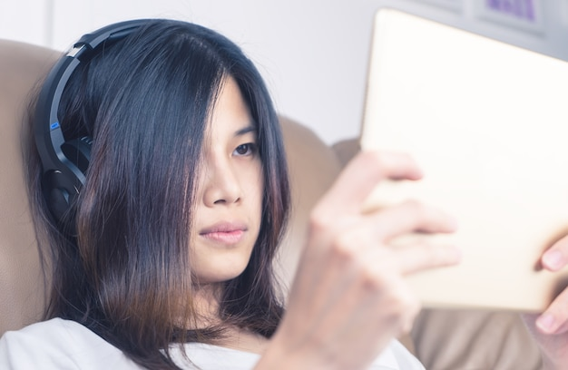 Asiatisches mädchen mit kopfhörer passt inhalt auf tablette auf
