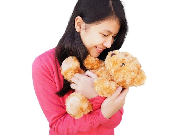Asiatisches mädchen mit langen haaren, die rosa hemd tragen und zu braunem teddybär in ihrer armumarmungshaltung lächeln, lokalisieren
