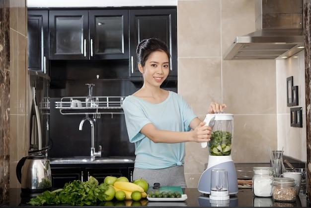 Asiatisches mädchen mit mixer in der küche