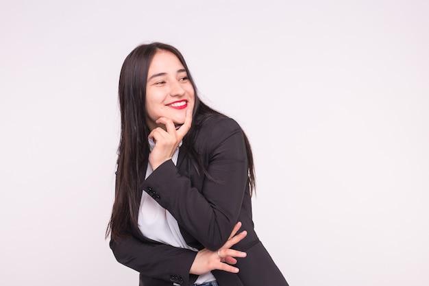 Asiatisches mädchen mit roten lippen in der lustigen pose, die schwarzen anzug in weiß mit kopienraum trägt.