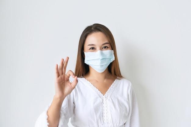 Asiatisches mädchen mit schützender gesichtsmaske, die fein in gebärdensprachhand zeigt