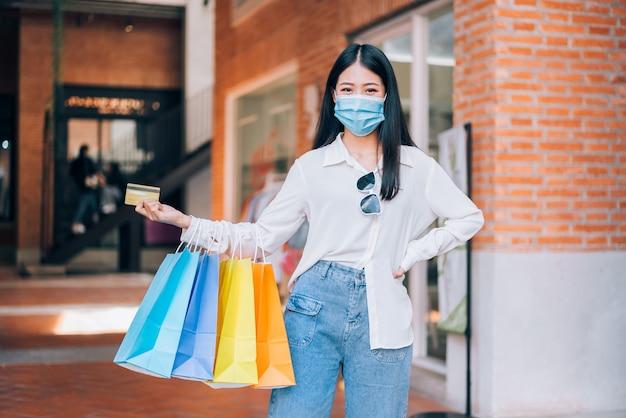 Asiatisches mädchen mit schutzmaske glücklich lächelnd mit kreditkarte und einkaufstüten and