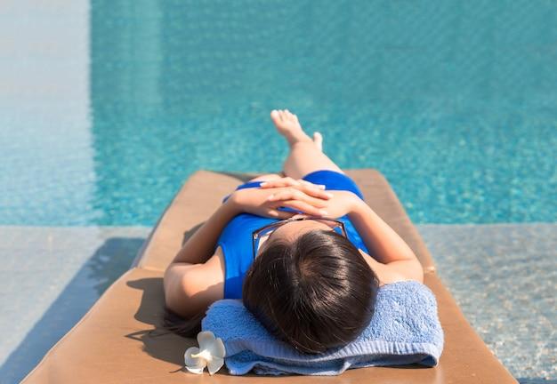 Asiatisches mädchen mit schwimmenreihe und sonnenbrillen auf pool