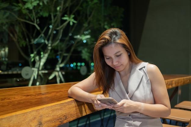 Asiatisches mädchen mit smartphone, frau, die handy beobachtet