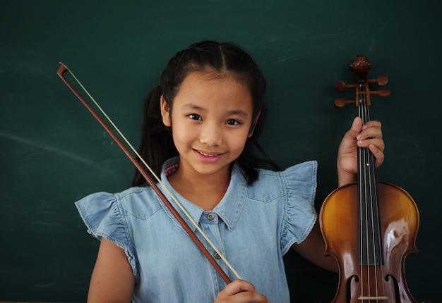Asiatisches mädchen mit violine auf tafelhintergrund