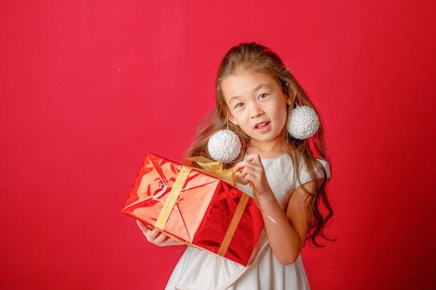 Asiatisches mädchen mit weihnachtsbaumspielzeug auf rotem hintergrund, weihnachten