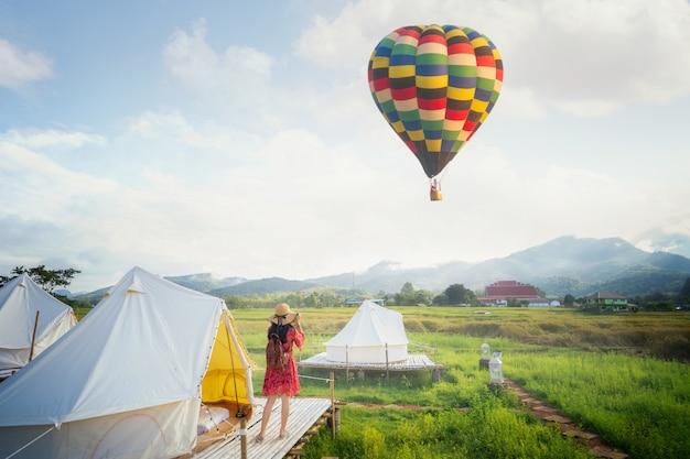 Asiatisches mädchen nehmen ein heißluftballonfoto durch kamera in landschafts-gastfamilie auf