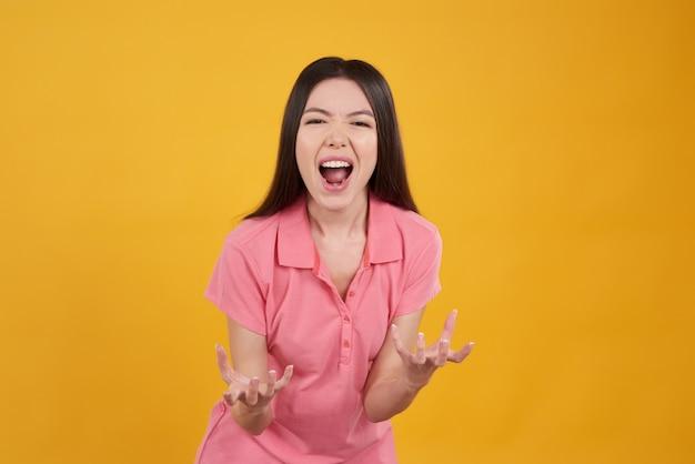 Asiatisches mädchen posiert schreiend auf gelb.