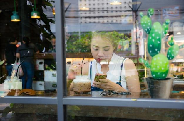 Asiatisches mädchen schaut smartphone im café