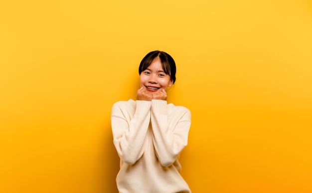 Asiatisches mädchen schön, das ein weißes freizeitkleid auf einem gelben hintergrund trägt. feiern sie den sieg mit einem glücklichen lächeln und dem siegerausdruck mit erhobener hand. glücklicher ausdruck