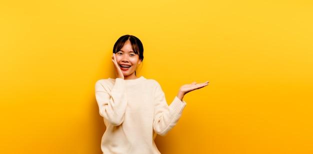 Asiatisches mädchen schön, das ein weißes freizeitkleid auf einem gelben hintergrund trägt. feiern sie den sieg mit
