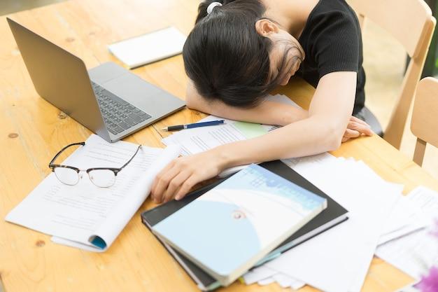 Asiatisches mädchen sehr erschöpft nach dem arbeiten mit laptop-computer