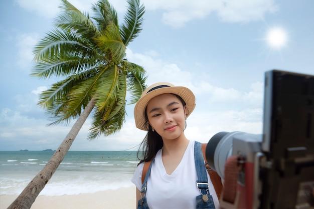 Asiatisches mädchen selfie durch digitalkamera mit strand und kokosnuss