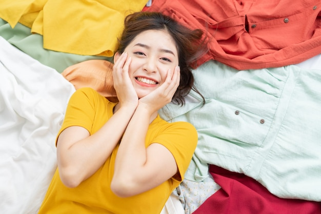 Asiatisches mädchen steckte in ihrem kleidergewirr fest