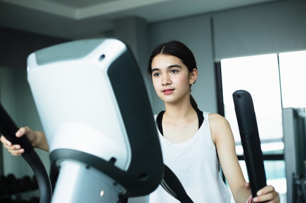 Asiatisches mädchen übung elliptisches cardio-lauftraining im fitnessstudio, das gewichtsverlust mit maschine aerobic für schlanken und festen gesunden lebensstil nimmt