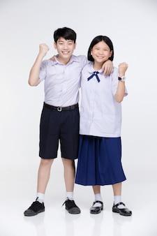 Asiatisches mädchen und junge in der uniform des studenten auf grau