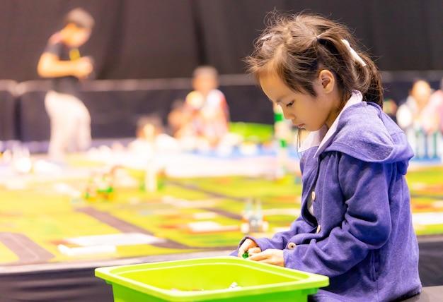 Asiatisches mädchen und junge spielt mit pädagogischem spielzeug