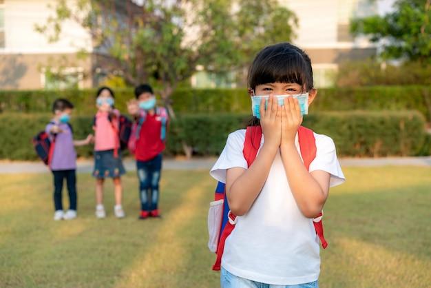 Asiatisches mädchen vorschulkindschüler, der gesundes gesichtsmaskenniesen mit freunden im hintergrund trägt.