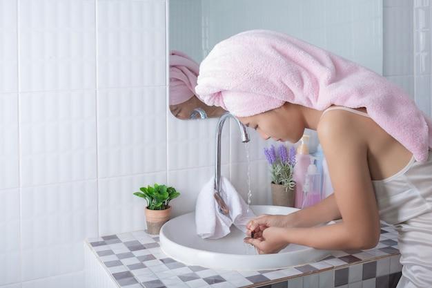Asiatisches mädchen wäscht gesicht.
