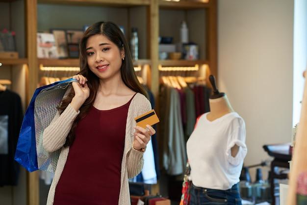 Asiatisches mädchen, welches die plastikkarte und einkaufstasche stehen im kleidungsspeicher hält