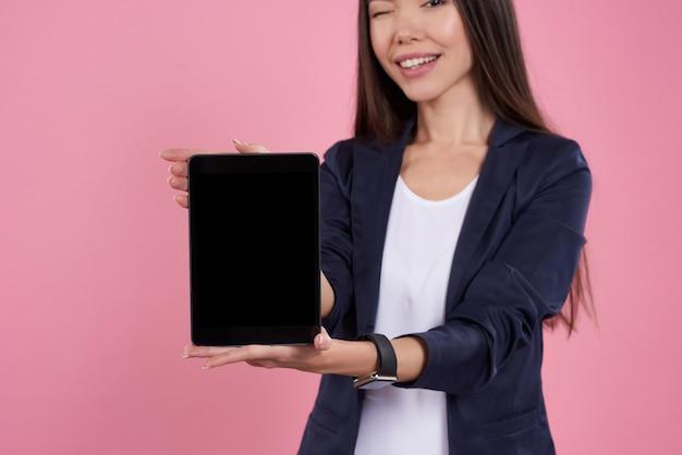 Asiatisches mädchen wirft mit der schwarzen lokalisierten tablette auf.