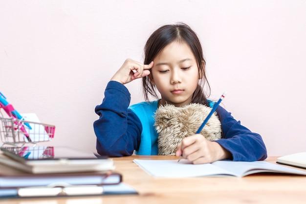 Asiatisches mädchenkind tun die hausarbeit sehr ernst beim denken der antwort