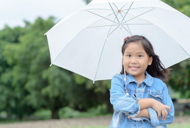 Asiatisches mädchenlächeln und weißen regenschirm halten