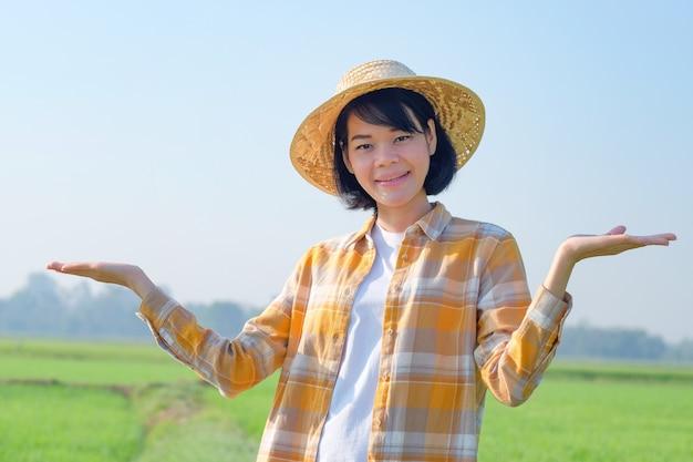 Asiatisches mädchenreisenderlächeln und erhobene hand an der grünen reisfarm