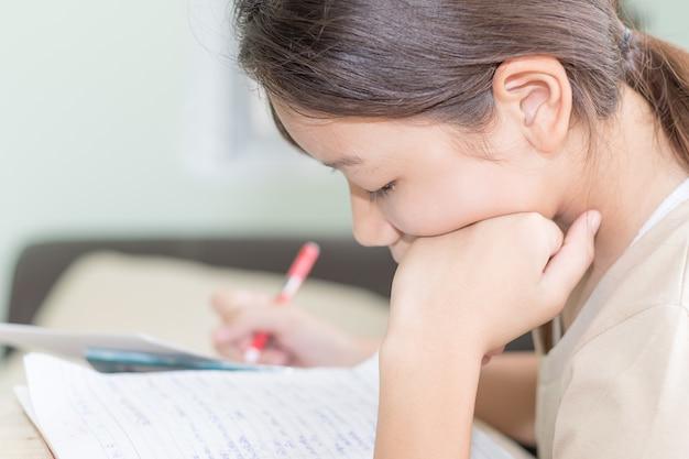 Asiatisches mädchenschreiben auf lehrbuch