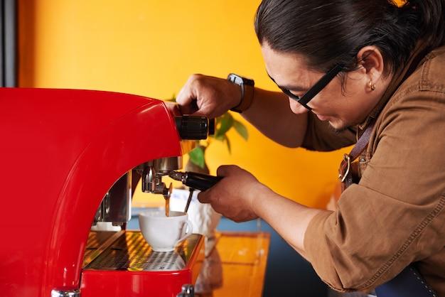 Asiatisches männliches barista, das tasse kaffee auf espressomaschine macht