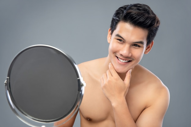 Asiatisches männliches baumuster, das sich sicher im spiegel schaut