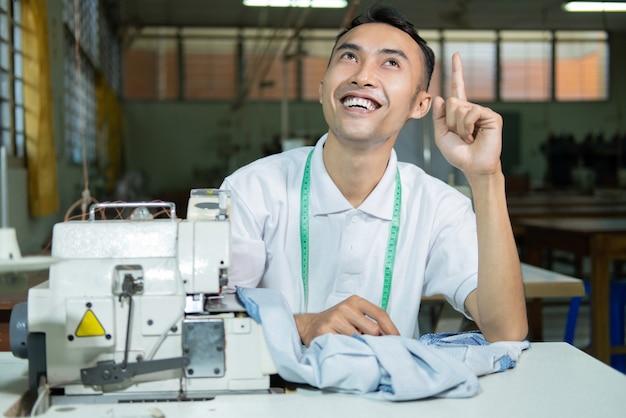 Asiatisches männliches schneiderlächeln mit nach oben zeigender hand, um etwas beim nähen mit nähmaschine zu präsentieren