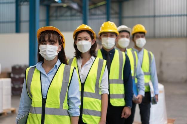Asiatisches männliches und weibliches ingenieurteam trägt eine maske mit helmsicherheitsständer in einer reihe in der lagerfabrik