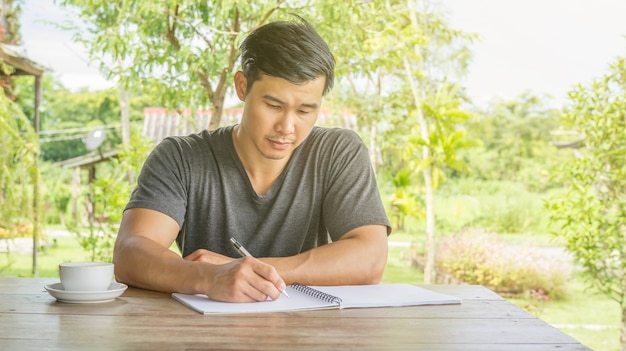 Asiatisches mannschreiben auf einem notizbuch in einem café.