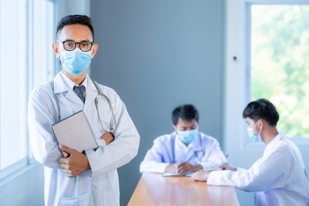 Asiatisches medizinisches team, das teammaskenkonzept des medizinischen masken-technologie-netzwerknetzes trägt.