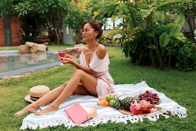 Asiatisches modell, das auf decke sitzt, wein trinkt und sommerpicknick im tropischen garten genießt. frisches obst, croissants und bücher.