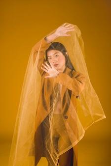 Asiatisches modell des mittleren schusses, das mit gelbem hintergrund aufwirft
