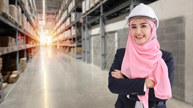 Asiatisches muslimisches arbeiterfrauenporträt, das im anzug mit selbstbewusstsein steht und die kamera mit großem lagerhintergrund betrachtet