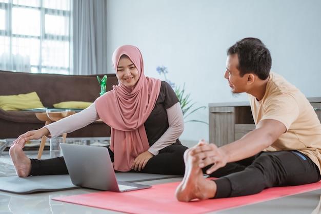 Asiatisches muslimisches fitnesspaar, das sich streckt und online-video-tutorial über laptop betrachtet