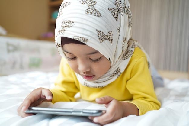 Asiatisches muslimisches kind, das zu hause smartphone spielt.