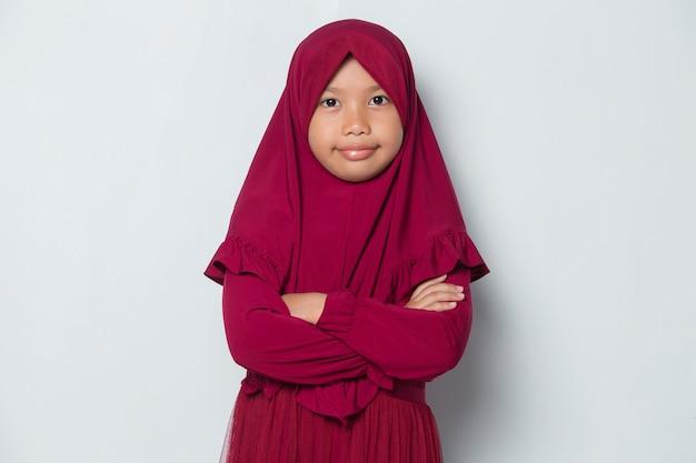 Asiatisches muslimisches kleines mädchen im kopftuch lächeln mit verschränkten armen