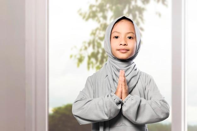 Asiatisches muslimisches mädchen im schleier mit grußgeste zu hause