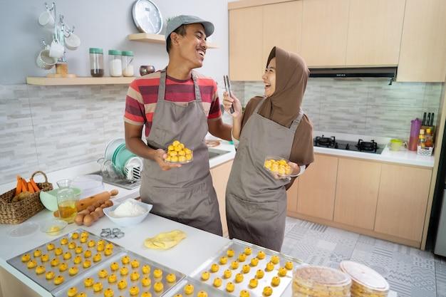Asiatisches muslimisches paar, das nastar-imbisskuchen zusammen in der küche macht