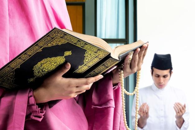 Asiatisches muslimisches paar, das steht, während erhobene hände und zusammen zu hause beten