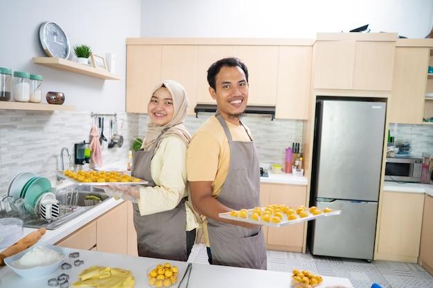 Asiatisches muslimisches paar, das während des ramadan für eid-feier zusammen in der küche nastar-snack-kuchen macht