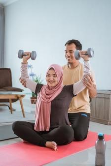 Asiatisches muslimisches paar, das zu hause gewicht trainiert und hebt. ehemann hilft seiner frau beim training